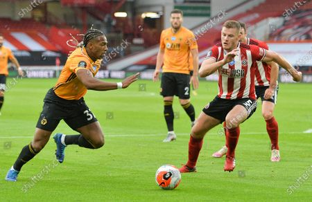 Jack O'Connell (R) of Sheffield in action against Adama Traore (L) of Wolverhampton during the English Premier League match between Sheffield United and Wolverhampton Wanderers in Sheffield, Britain, 08 July 2020.