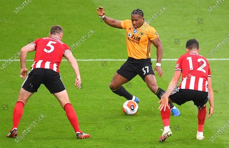 Jack O'Connell (L) and John Egan (R) of Sheffield in action against Adama Traore (C) of Wolverhampton during the English Premier League match between Sheffield United and Wolverhampton Wanderers in Sheffield, Britain, 08 July 2020.