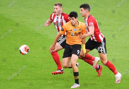 Jack O'Connell (L) and John Egan (R) of Sheffield in action against Raul Jimenez (C) of Wolverhampton during the English Premier League match between Sheffield United and Wolverhampton Wanderers in Sheffield, Britain, 08 July 2020.