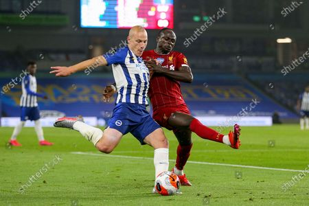 Brighton and Hove Albion midfielder Aaron Mooy (18) battles crosses from Liverpool forward Sadio Mane (10) during the Premier League match between Brighton and Hove Albion and Liverpool at the American Express Community Stadium, Brighton and Hove