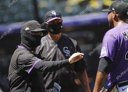 From left, Colorado Rockies pitching coach Steve Foster and manager Bud Black confer with relief pitcher Jose Mujica after drills as the team practices, in Denver