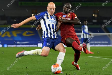 Brighton's Aaron Mooy (L) in action against Liverpool's Sadio Mane (R) during the English Premier League match between Brighton & Hove Albion and Liverpool FC in Brighton, Britain, 08 July 2020.