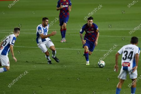 Barcelona's Lionel Messi runs for the ball next to Espanyol's David Lopez, left, during the Spanish La Liga soccer match between FC Barcelona and RCD Espanyol at the Camp Nou stadium in Barcelona, Spain