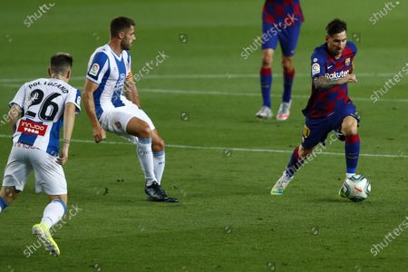 Barcelona's Lionel Messi runs for the ball next to Espanyol's David Lopez and Pol Lozano during the Spanish La Liga soccer match between FC Barcelona and RCD Espanyol at the Camp Nou stadium in Barcelona, Spain