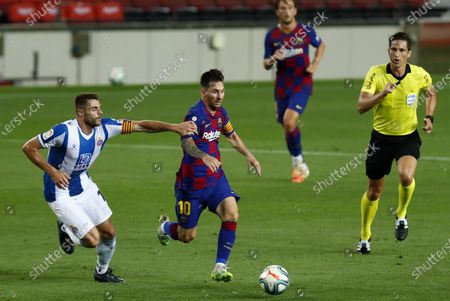 Barcelona's Lionel Messi runs for the ball next to Espanyol's David Lopez during the Spanish La Liga soccer match between FC Barcelona and RCD Espanyol at the Camp Nou stadium in Barcelona, Spain