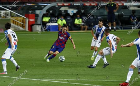 Barcelona's Lionel Messi runs for the ball against Espanyol's Leandro Cabrera, Marc Roca and David Lopez during the Spanish La Liga soccer match between FC Barcelona and RCD Espanyol at the Camp Nou stadium in Barcelona, Spain