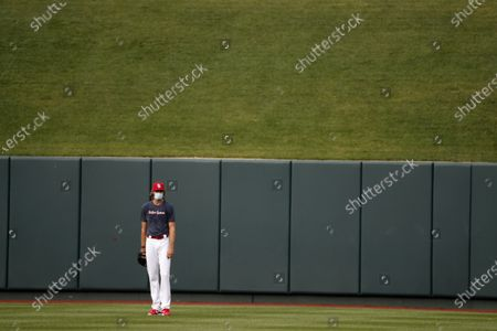 St. Louis Cardinals pitcher Andrew Miller wears a face mask as he stands in the outfield during baseball practice at Busch Stadium, in St. Louis
