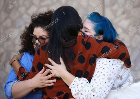 """Viri Hernandez, middle, director of Poder In Action, hugs James Garcia's sisters, Jacqueline Fernandez, left, and Elizabeth Garcia during a news conference in front of Phoenix Police headquarters in Phoenix on . The Phoenix Police chief is asking the FBI to investigate a man's shooting death at the hands of officers. Chief Jeri Williams announced Tuesday that she is requesting the agency conduct an independent probe to see if 28-year-old James """"Jay"""" Garcia's civil rights were violated during the July 4 shooting"""