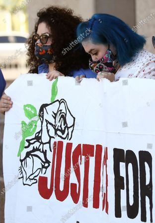 Jacqueline Fernandez, left, and Elizabeth Garcia, sisters of James Garcia who was shot and killed by Phoenix Police, hold up a sign during a news conference demanding the release of police body cam footage, in Phoenix, in the Phoenix Police shooting death of their brother. Phoenix Police Chief Jeri Williams announced Tuesday that she is requesting the agency conduct an independent probe to see if 28-year-old Garcia's civil rights were violated during the July 4 shooting
