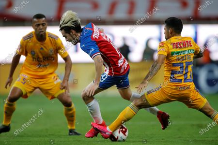 Jesus Angulo (C) of Chivas in action against Javier Aquino (R) of Tigres during a GNP Cup for Mexico match between Chivas and Tigres, in Guadalajara, Jalisco state, Mexico, 08 July 2020 (issued 09 July 2020).