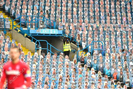 A steward at Elland Road celebrates her teams 5-0 victory over Stoke City among the sea of 15000 cut outs of fans in the Stadium