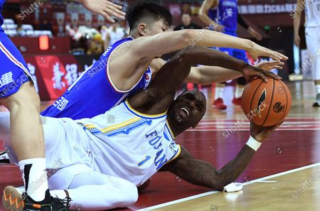 Ty Lawson (bottom) of Fujian Sturgeons vies with Meng Zikai of Tianjin Pioneers during a match between at the 2019-2020 Chinese Basketball Association (CBA) league in Qingdao, east China's Shandong Province, July 9, 2020.