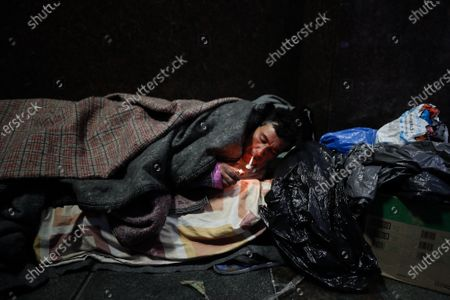 Juan Sebastian Aguirre lights a cigarette as he tries to warm himself with blankets in the bed he made on the street a few meters from the Government House, in Buenos Aires, Argentina, 08 July 2020 (issued 09 July 2020). The streets of Buenos Aires are home to a multitude of people, a figure that ranges between 1,600 and 7,200 according to sources, who now see their daily problems aggravated by the arrival of cold winter and the pandemic. On 01 June, the city government began the Cold Operation, which will last until 31 August, in which more than 1,220 people distribute food, hygiene items and blankets to homeless people, to whom they inform and offer the possibility of going to one of the 43 Inclusion Centers, known as paradores, which the capital has, with a total of 2,987 beds available.
