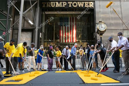 New York Mayor Bill de Blasio, wearing orange mask, participates in painting Black Lives Matter on Fifth Avenue in front of Trump Tower, in New York