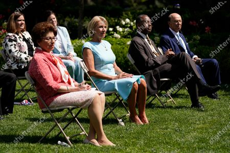 """Front row from left, Jovita Carranza, administrator of the Small Business Administration, Education Secretary Betsy DeVos, Housing and Urban Development Secretary Ben Carson and Commerce Secretary Wilbur Ross listen as President Donald Trump speaks before signing an executive order on the """"White House Hispanic Prosperity Initiative,"""" in the Rose Garden of the White House, in Washington"""