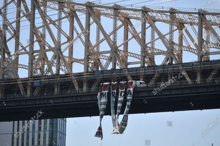 A banner protesting police brutality hangs from the Queensboro Bridge in New York.