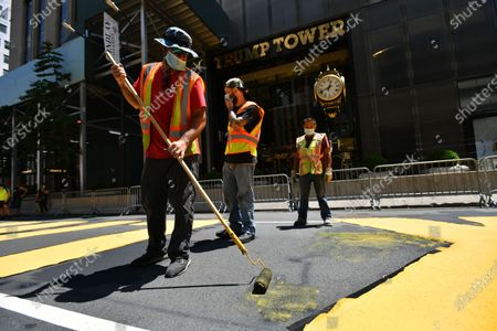 Stock Picture of City workers paint a new Black Lives Matter mural outside of Trump Tower on Fifth Avenue in New York.
