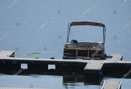"""Yellow police tape appears near an empty boat on a dock on Lake Piru, Calif., during the search for former """"Glee"""" actress Naya Rivera, . Rivera rented a boat on Wednesday and her 4-year-old son was found alone on the rented boat"""