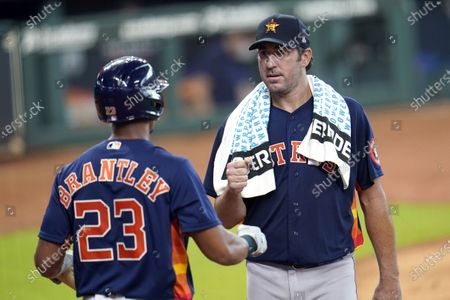 Houston Astros starting pitcher Justin Verlander, right, talks with left fielder Michael Brantley (23) during a simulated baseball game, in Houston