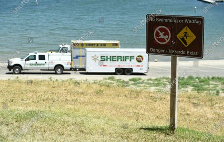 """Sign indicating hazards appears as members of Ventura County Sheriff's Office Underwater Search and Rescue Team search for former """"Glee"""" actress Naya Rivera, in Lake Piru, Calif. Rivera rented a boat on Wednesday and her 4-year-old son was found alone on the rented boat"""