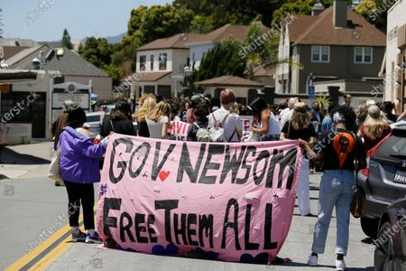 Two women hold up a banner urging Gov. Gavin Newsom to free prisoners during a news conference outside San Quentin State Prison, in San Quentin, Calif. A group of legislators, advocates, academics and public health officials gathered at San Quentin State Prison to discuss a COVID-19 outbreak at the facility that has sickened more than 1,400 inmates with six deaths