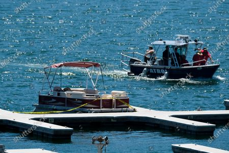 """Yellow police tape appears near an empty boat on a dock as members of the Ventura County Sheriff's Office in a patrol boat search for former """"Glee"""" actress Naya Rivera, in Lake Piru, Calif. Rivera rented a boat on Wednesday and her 4-year-old son was found alone on the rented boat"""