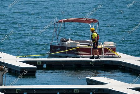 """Member of Ventura County Sheriff's Office Underwater Search and Rescue Team checks an empty boat on a dock in searching for former """"Glee"""" actress Naya Rivera, in Lake Piru, Calif. Rivera rented a boat on Wednesday and her 4-year-old son was found alone on the rented boat"""