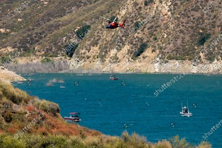 """Helicopter joins members of Ventura County Sheriff's Office Underwater Search and Rescue Team in the search for former """"Glee"""" actress Naya Rivera, at Lake Piru in Los Padres National Forest, northwest of Los Angeles. Rivera rented a boat Wednesday and her 4-year-old son was found alone on the boat"""