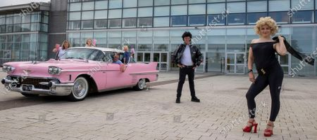 A series of drive-in movies are being shown on the boardwalk at intu Braehead later this month. Picture shows Scott Martin and Lauren Little from intu Braehead Arena dressed as Danny and Sandy, from the Grease movie Ð one of the films being shown Ð with the Gordon family from Paisley at a pink Cadillac car on the boardwalk. ..