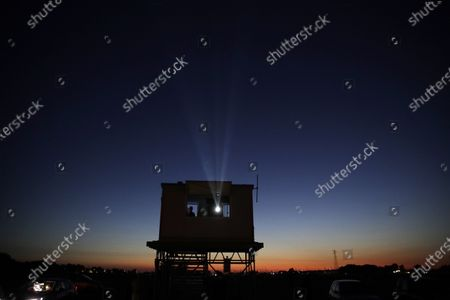 """People in their cars watch the movie """"Tolo Tolo"""", at the Paolo Ferrari drive-in cinema in Ostia, on the Rome's seaside. The drive-in cinema that could host up to 460 cars and 50 motorbikes started this weekend to aid in social distancing amid the COVID-19 pandemic"""