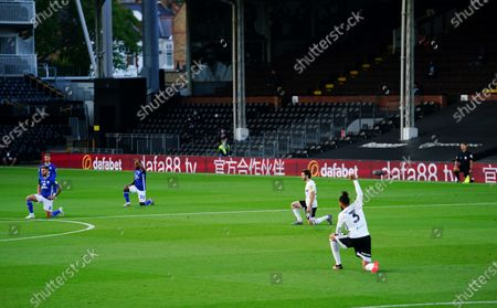 Michael Hector of Fulham takes the knee along with Harry Arter, Cardiff players and the officials