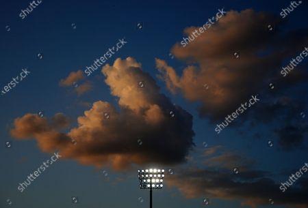 Clouds pass over a lit floodlight
