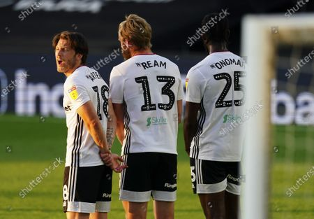 Harry Arter of Fulham instructs from a there man wall
