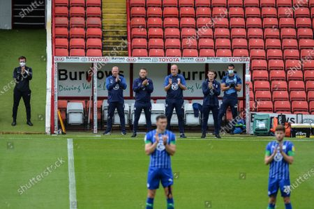Paul Cook manager of Wigan Athletic and his staff take part in the minutes applause for Jack Charlton prior to kick off.