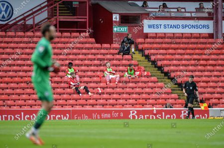 Barnsley FC substitutes watch from the stands.