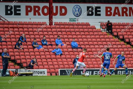 Paul Cook manager of Wigan Athletic and his substitutes look on from the stands.