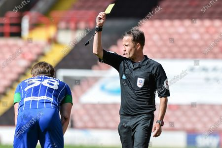 Referee David Webb gives Joe Gelhardt (38) of Wigan Athletic a yellow card