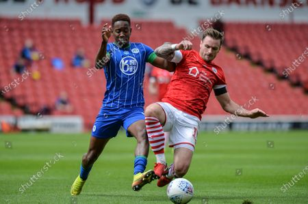 Jamal Lowe (9) of Wigan Athletic and Cauley Woodrow (9) of Barnsley FC compete for the ball