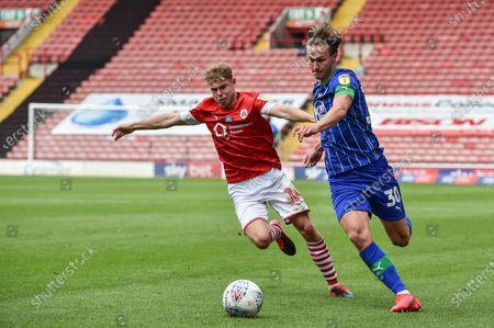 Kilian Ludewig (14) of Barnsley FC and Kieran Dowell (30) of Wigan Athletic challenge for the ball.