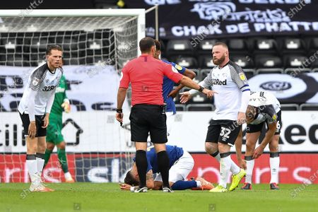 Wayne Rooney (32) of Derby County challenges Referee Tim Robinson after a free kick is awarded to Brentford