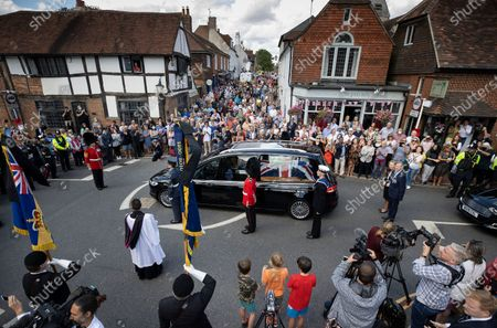 Crowds fill the High Street as the funeral cortege carrying the body of WWII Forces' Sweetheart Dame Vera Lynn passes through her home village of Ditchling, East Sussex. The cortege will head to a crematorium in Brighton for a private funeral. A Battle of Britain Memorial Flight flypast, consisting of a Spitfire and a Hurricane, will perform a flypast at noon.