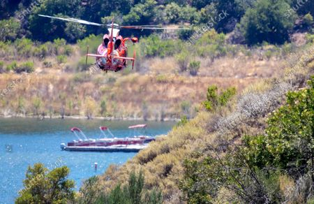 A US Coast Guard helicopter searches along the Lake Piru shoreline for missing actress Naya Rivera on Thursday, July 9, 2020 in Lake Piru, CA. (Brian van der Brug / Los Angeles Times)