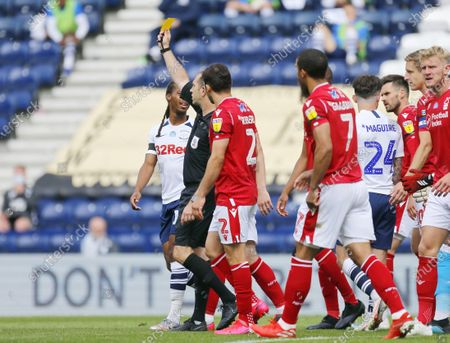 Photo libre de droits de Deepdale Stadium, Preston, Lancashire, England; Referee Jeremy Simpson shows a yellow card to Andrew Hughes of Preston North End with both teams arguing his decision; English Championship Football, Preston North End versus Nottingham Forest.