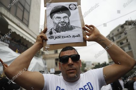 "Hezbollah supporter holds a placard depicting its leader Sayyed Hassan Nasrallah, during a protest against U.S. interference in Lebanon's affairs, near the U.S. embassy, in Aukar northeast of Beirut, Lebanon, . The Arabic words on the placard read:""Sayyed Hassan Nasrallah"