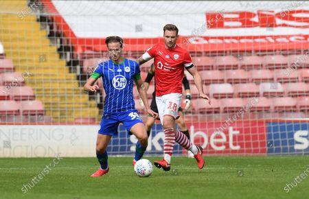 Barnsley's Michael Sollbauer keeps an eye on Wigan's Kieran Dowell.