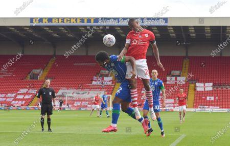 Barnsley's Elliot Simoes outjumps Wigan's Cedric Kipre.