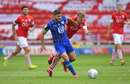 Barnsley's Kilian Ludewig is pushed off the ball by Wigan's Sam Morsey.