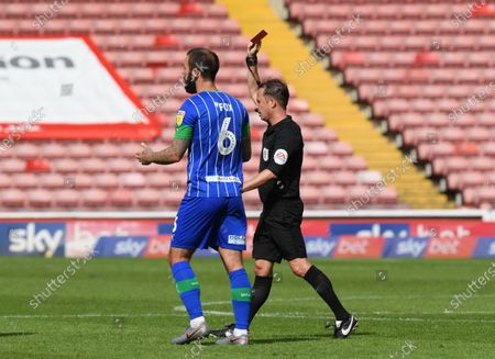 Wigan's Danny Fox is sent off for a challenge on Elliot Simoes.