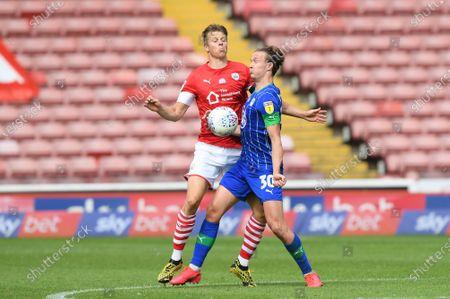 Barnsley's Mads Andersen with Wigan's Kieran Dowell.