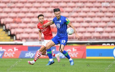 Wigan's Kieffer Moore holds off Jordan Williams.